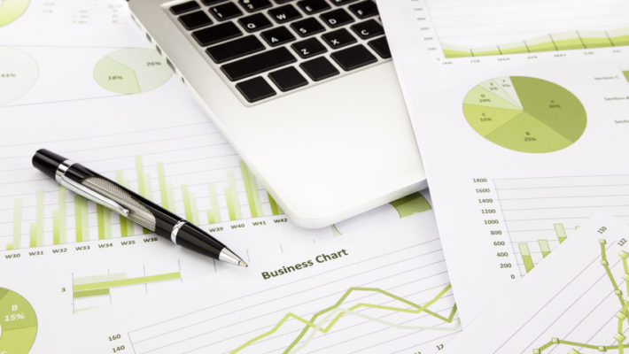 laptop and pen with green business charts, graphs, information and reports background for financial and business concepts
